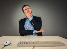 Handsome man sitting at a desk and looking up Royalty Free Stock Photos