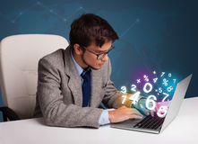 Handsome man sitting at desk and typing on laptop with 3d number Royalty Free Stock Images