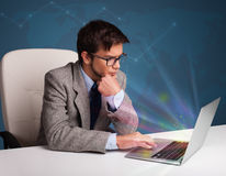 Handsome man sitting at desk and typing on laptop with abstract Royalty Free Stock Photography