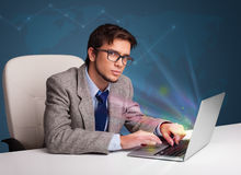 Handsome man sitting at desk and typing on laptop with abstract Royalty Free Stock Photo