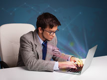 Handsome man sitting at desk and typing on laptop with abstract Stock Image