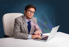 Handsome man sitting at desk and typing on laptop with abstract Royalty Free Stock Images