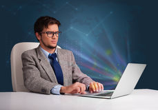 Handsome man sitting at desk and typing on laptop with abstract Royalty Free Stock Photos