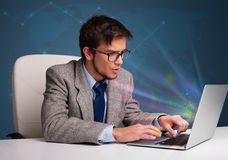 Handsome man sitting at desk and typing on laptop with abstract Stock Photography