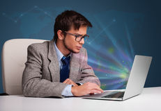 Handsome man sitting at desk and typing on laptop with abstract Stock Photos