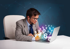 Handsome man sitting at desk and typing on laptop with 3d number Royalty Free Stock Photo