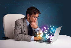 Handsome man sitting at desk and typing on laptop with 3d number Stock Images