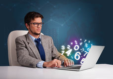 Handsome man sitting at desk and typing on laptop with 3d number Stock Photos