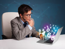 Handsome man sitting at desk and typing on laptop with 3d number Stock Photo