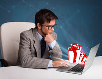 Handsome man sitting at desk and typing on laptop with present b Royalty Free Stock Photos