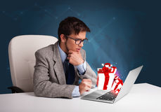 Handsome man sitting at desk and typing on laptop with present b Stock Photo