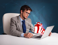 Handsome man sitting at desk and typing on laptop with present b Stock Images