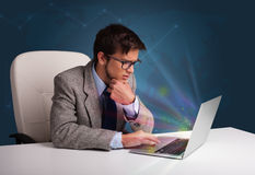 Handsome man sitting at desk and typing on laptop Stock Photography