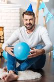 Handsome man sitting on the floor and holding balloon Royalty Free Stock Photo
