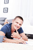 A handsome man sitting on the floor in the living room. Royalty Free Stock Photography
