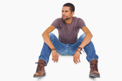 Handsome man sitting on floor and looking away Stock Photo