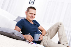 A handsome man sitting on the floor taking notes at his home. Royalty Free Stock Photography