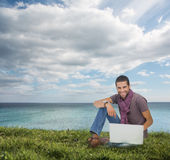 Handsome man sitting on the grass Royalty Free Stock Photography