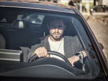 Handsome man sitting in his car. Portrait of attractiave man in business suit sitting in his new stylish car outdoor in city Royalty Free Stock Images