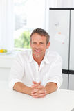 Handsome man sitting in his kitchen Stock Images