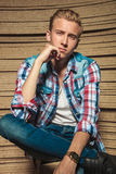 Handsome man sitting legs crossed while touching his chin Royalty Free Stock Photo