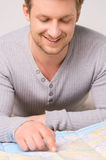 Handsome man sitting and looking at map. Royalty Free Stock Photography