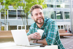Handsome man sitting outdoors with laptop and coffee royalty free stock photos