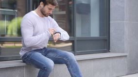 Handsome Man Sitting Outside Office Using Smartwatch for Browsing. 4k , high quality stock video