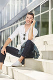 Handsome man sitting outside talking on mobile phone Royalty Free Stock Image
