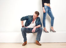 Handsome man sitting with a pair of female legs in background Royalty Free Stock Photo