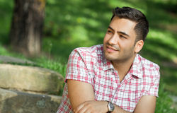Handsome man sitting in a park Stock Images