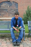 Thoughts of Love. Handsome man sitting on a park bench holding a pink rose bud Stock Images