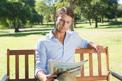 Handsome man sitting on park bench reading newspaper Stock Photos