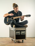 Handsome man sitting and playing guitar Stock Image