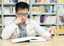 Handsome man sitting and reading in library Stock Photography
