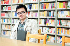 Handsome man sitting and reading in library Royalty Free Stock Images
