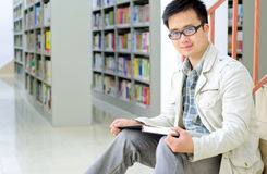 Handsome man sitting and reading in library Stock Photos