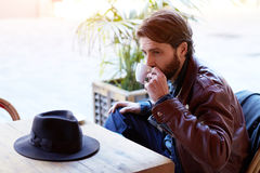 Handsome man sitting in restaurant and waiting for a friend who had forgotten his hat. Portrait of handsome fashionable hipster man drinking tea or coffee while royalty free stock photo