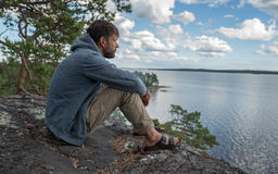 Handsome man is sitting on the rock and looking into the distance Stock Photo