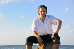 Handsome man sitting by the sea Stock Image