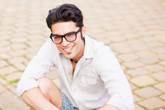 Handsome man sitting on the sidewalk smiling Royalty Free Stock Images