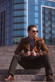 Handsome man is sitting on a skyscraper background Stock Photos