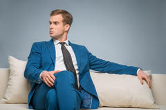 Handsome man sitting on the sofa Stock Photography