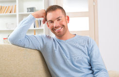 Handsome man sitting on the sofa Royalty Free Stock Photos