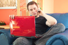 Handsome man sitting on sofa with phone and laptop Stock Images