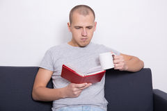 Handsome man sitting on sofa and reading book with cup of tea Stock Photo