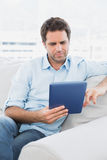 Handsome man sitting on the sofa using his tablet pc Stock Photos
