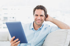 Handsome man sitting on the sofa using his tablet pc smiling at camera Stock Photo