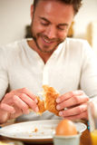 Handsome man sitting at table eating breakfast Royalty Free Stock Photography