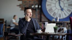 Handsome man sitting at the table in restaurant and speaking on the telephone. Stylish young student spending leisure stock footage
